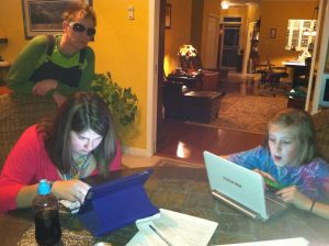 Two young ladies are working on an IPad and netbook during a VIBES technology session.