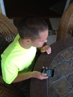 Picture of a young man getting a lesson using an Apple IPod Touch that uses Voice Over screen reading to help the blind.